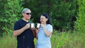 愉快的夫妇男人和妇女森林饮用的茶的边缘的 股票录像