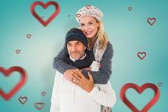 愉快的夫妇的综合图象在冬天塑造拥抱 库存照片