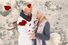 愉快的夫妇的综合图象在冬天塑造拥抱 免版税库存图片