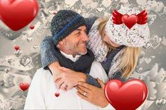 愉快的夫妇的综合图象在冬天塑造拥抱 免版税库存照片