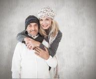 愉快的夫妇的综合图象在冬天塑造拥抱 图库摄影