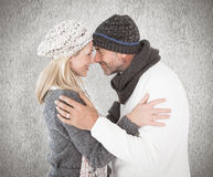 愉快的夫妇的综合图象在冬天塑造拥抱 免版税图库摄影