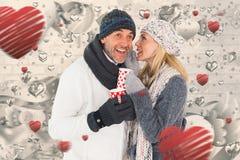 愉快的夫妇的综合图象在冬天塑造拿着杯子 免版税库存照片