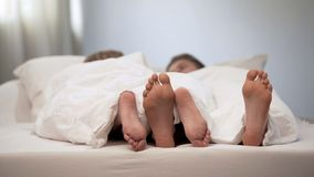 愉快的夫妇脚在蜜月床上,可爱的交谈在早晨,婚姻 免版税库存照片