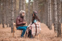 愉快的夫妇花费坐在秋天森林里,聊天和喝从杯子的时间茶 免版税库存照片