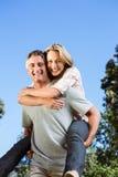 愉快的夫妇获得乐趣在公园 免版税库存照片