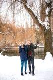 愉快的夫妇获得乐趣在冬天公园 免版税库存照片