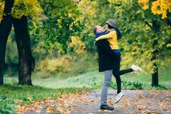 愉快的夫妇获得乐趣在秋天公园 黄色树和叶子 室外笑的男人和的妇女 查出的黑色概念自由 免版税图库摄影