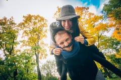 愉快的夫妇获得乐趣在秋天公园 黄色树和叶子 室外笑的男人和的妇女 查出的黑色概念自由 免版税库存照片