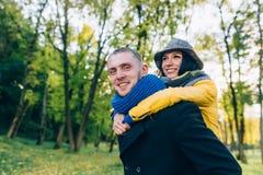 愉快的夫妇获得乐趣在秋天公园 黄色树和叶子 室外笑的男人和的妇女 查出的黑色概念自由 库存图片