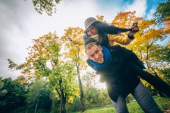愉快的夫妇获得乐趣在秋天公园 黄色树和叶子 室外笑的男人和的妇女 查出的黑色概念自由 库存照片