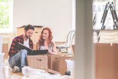 愉快的夫妇观看的photobook和包装的材料,当移动时 库存照片