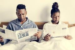 愉快的夫妇读书在床上 库存图片