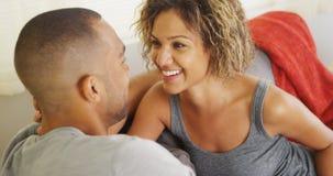 愉快的夫妇谈话在长沙发 库存照片