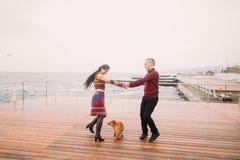 年轻愉快的夫妇走与狗和获得在多雨停泊处的乐趣在秋天 背景峡湾光芒海运星期日 免版税库存图片