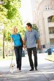 愉快的夫妇走的狗下来街道 免版税图库摄影