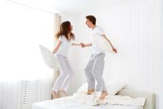 愉快的夫妇跳跃和获得乐趣在床上 免版税库存图片