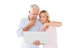 愉快的夫妇身分和一起使用膝上型计算机 免版税库存照片