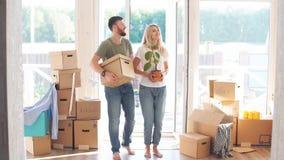 愉快的夫妇运载的纸板箱到新的家里在移动的天 股票录像
