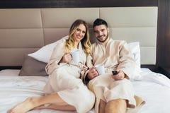 愉快的夫妇食用早餐在豪华酒店房间,看着电视 免版税库存照片