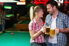 愉快的夫妇饮用的啤酒和使用落袋撞球 免版税库存照片