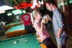 愉快的夫妇饮用的啤酒和使用落袋撞球 库存图片