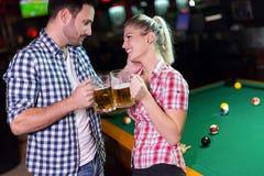 愉快的夫妇饮用的啤酒和使用落袋撞球 图库摄影