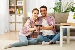 愉快的夫妇饮用的红酒在家 免版税库存照片