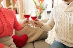 愉快的夫妇饮用的红酒在情人节 免版税图库摄影