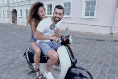 愉快的夫妇骑马全长侧视图在减速火箭的摩托车的 免版税库存图片