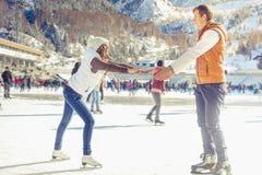 愉快的夫妇,女孩和男孩滑冰室外在溜冰场 库存图片