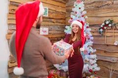 愉快的夫妇,新年,一个人给他的女朋友一个礼物盒,以圣诞树为背景 免版税图库摄影