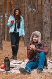 愉快的夫妇,温暖地穿戴,获得乐趣在冷的秋天森林 免版税库存照片