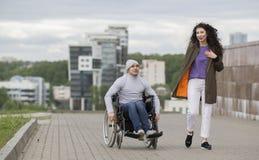 愉快的夫妇-一个轮椅的残疾年轻人有一起享受日落的少妇的 免版税库存照片