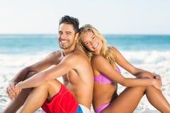 愉快的夫妇紧接坐海滩 免版税图库摄影