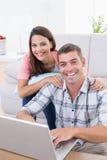 愉快的夫妇画象使用膝上型计算机的 免版税库存图片