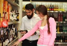 愉快的夫妇从陈列室商店选择酒精 库存图片