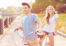 愉快的夫妇-骑在公园outdoo的男人和妇女一辆自行车 图库摄影