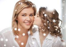 愉快的女儿亲吻她的母亲 免版税库存照片