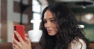 愉快的女商人谈话在电话有交谈通过视频聊天会议在舒适咖啡馆 女商人使用 股票视频