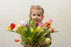 愉快的女婴在手上高兴并且微笑与多彩多姿的郁金香花束  免版税图库摄影