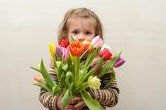 愉快的女婴在手上高兴并且微笑与多彩多姿的郁金香花束  免版税库存照片