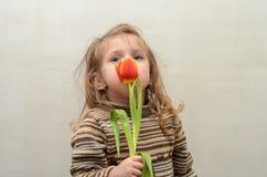 愉快的女婴在手上高兴并且微笑与多彩多姿的郁金香花束  免版税库存图片