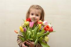 愉快的女婴在手上高兴并且微笑与多彩多姿的郁金香花束  库存照片