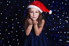 愉快的女孩与吹白色假雪 免版税库存图片