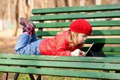 愉快的女孩与片剂个人计算机一起使用 免版税库存图片