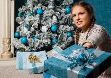 愉快的女孩举行圣诞节礼物箱子在假日早晨在美好的屋子内部里 女孩在手上的拿着Xmas礼物近 免版税库存照片