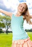 愉快的女孩享受温暖的夏日外面。 库存照片