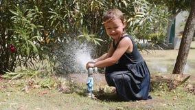 愉快的女孩使用与喷水从在草坪的管子 股票录像