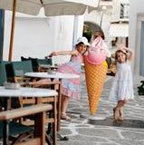 愉快的女孩和圆锥形的冰淇淋杯 免版税库存图片